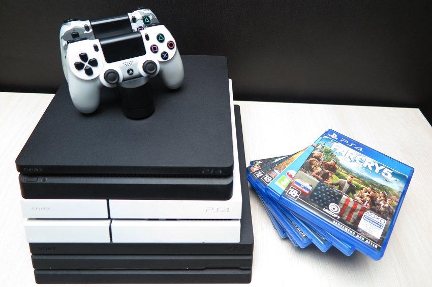 Игровые приставки playstation 4 на столе рядом с дисками